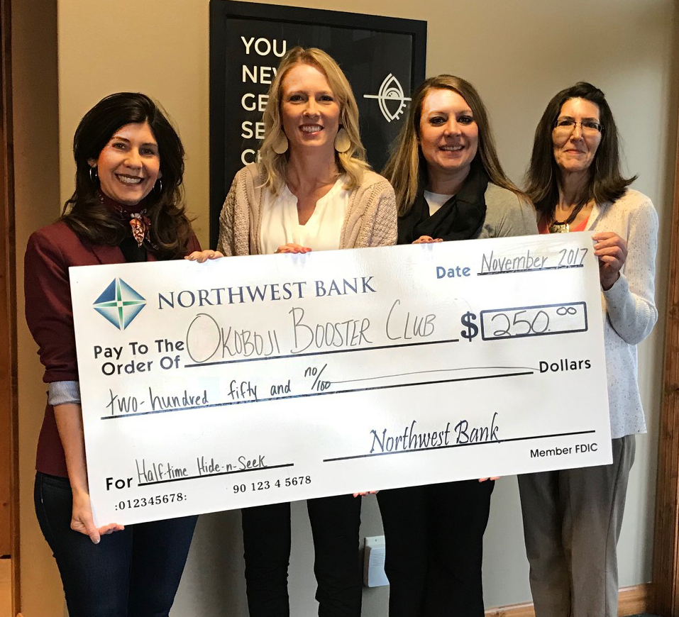 Image of Northwest Bank staff giving a donation check to Okoboji Booster club member Jill Harms