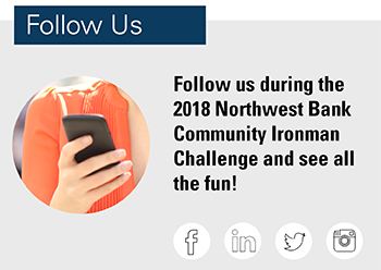 Image of a hand with a smartphone stating follow us during the 2018 Northwest Bank Ironman Challenge