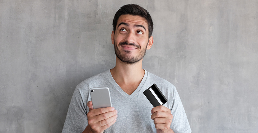 image of man holding credit card and phone