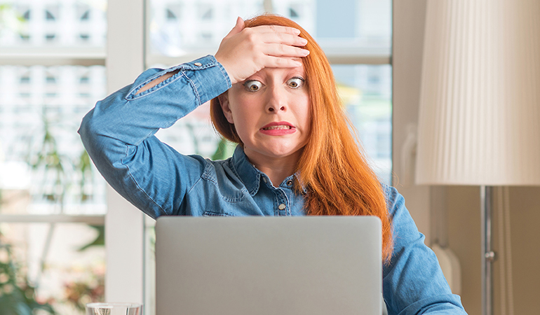 Image of woman looking at computer with hand on forehead