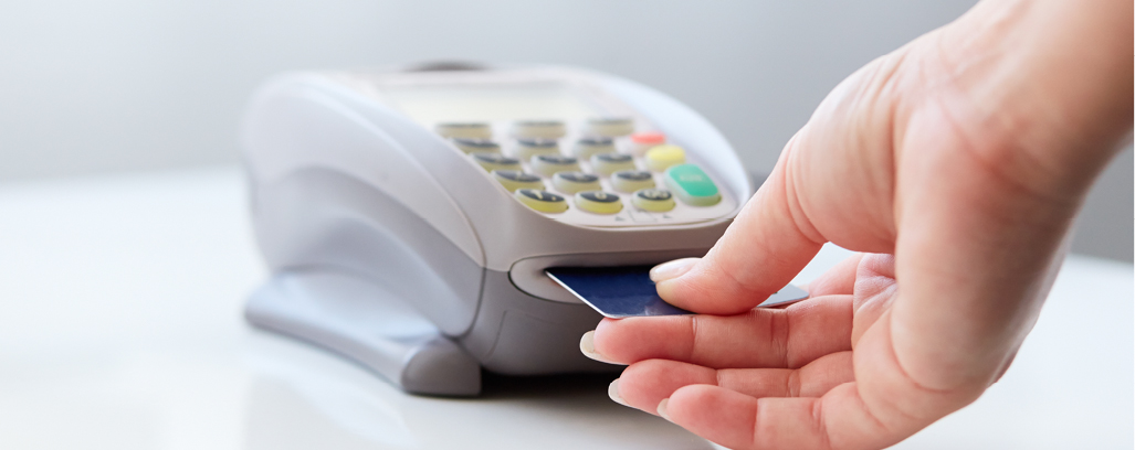 Image of a person using a debit card machine