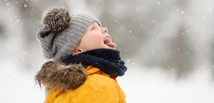 image of kid playing in the falling snow