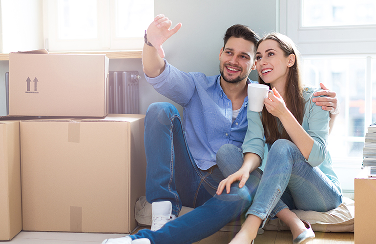 Image of a couple sitting by moving boxes
