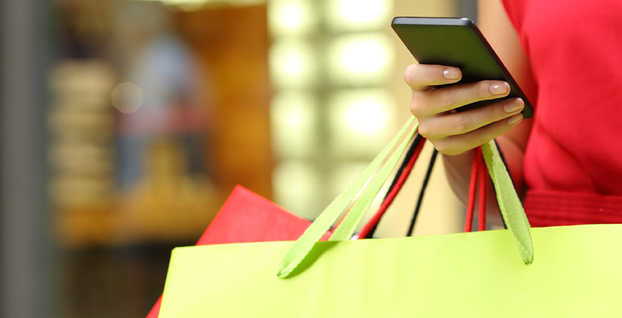 Image of a womans hand with a cell phone and shopping bags