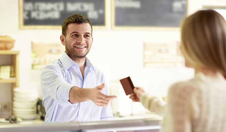 Image of a customer using a debit card at a store