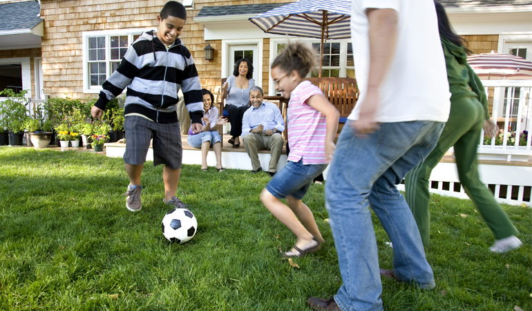 Image of a family playing soccer in a yard
