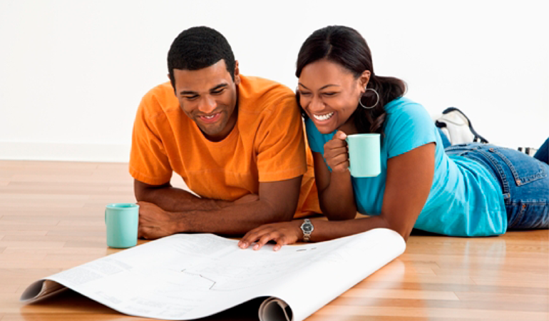 Image of a young couple looking at floor plans