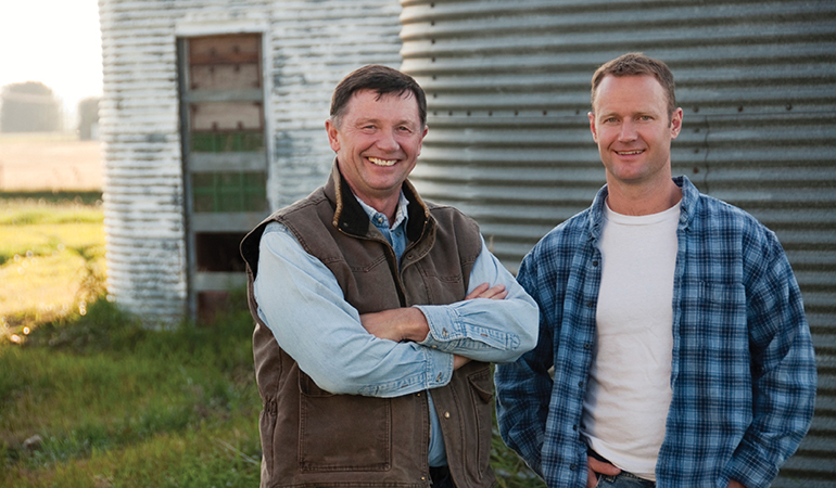 Image of two men standing in front of a silo