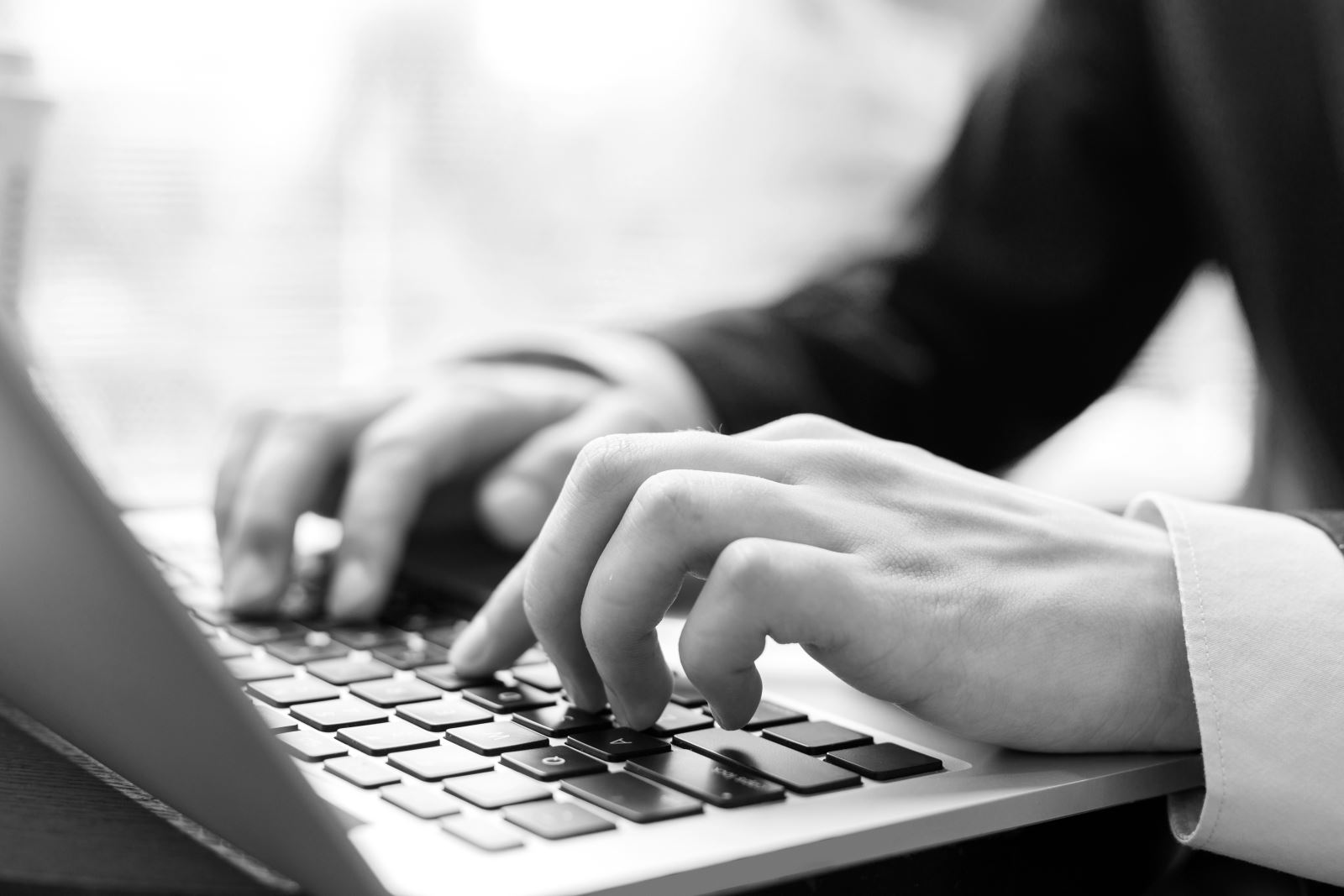 Black and white image of a man typing on a laptop