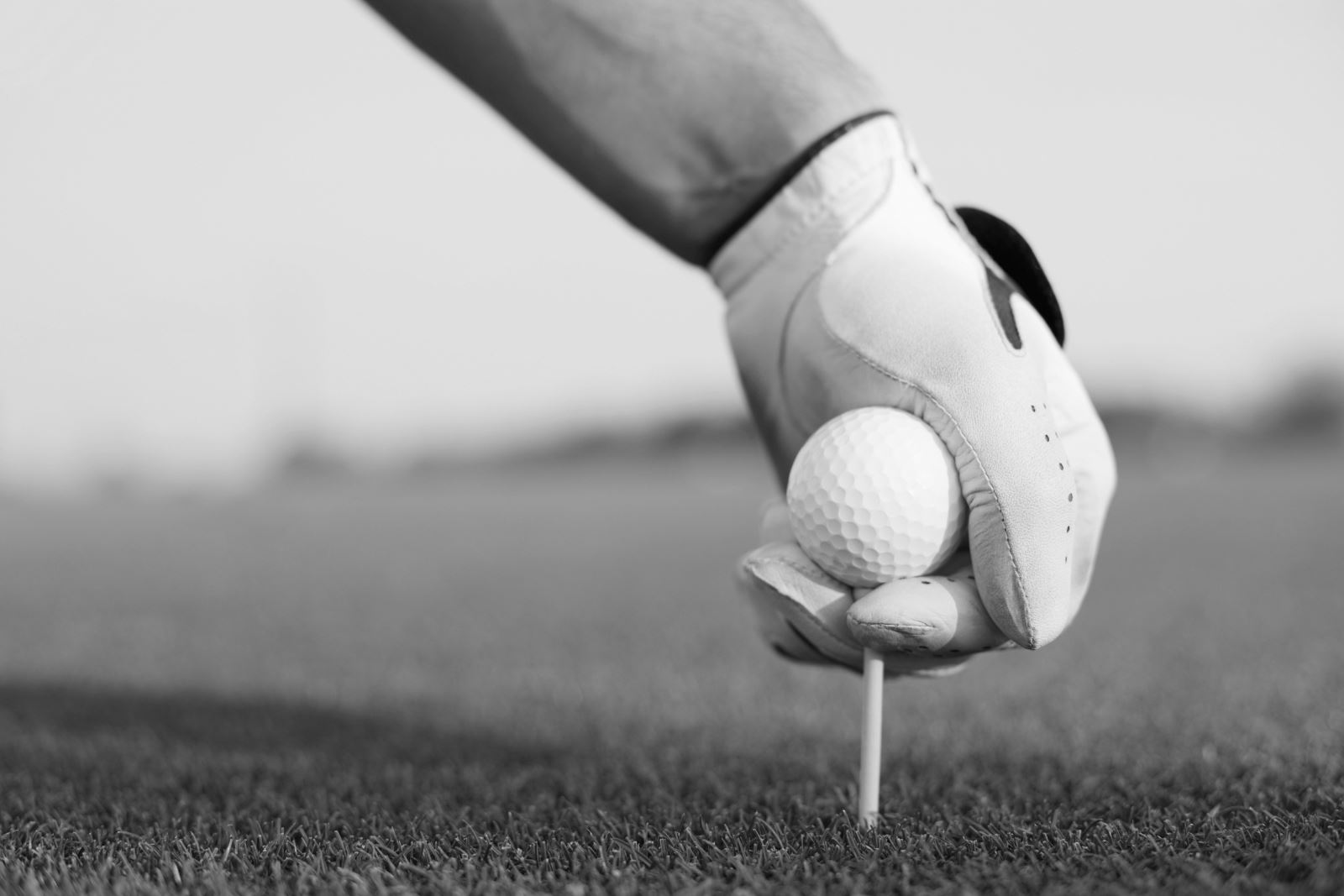 Black and white image of a man putting a golf ball and tee in the ground